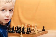 Le petit garçon apprennent à jouer aux échecs Photographie stock libre de droits