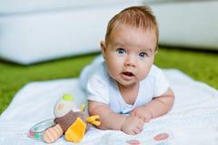 Le petit garçon aux yeux bleus se penche sur la poignée se trouvant sur le plancher de t Images stock
