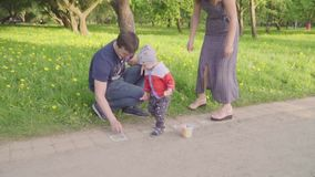 Le petit garçon avec de jeunes parents peint la craie sur l'asphalte Mouvement lent banque de vidéos