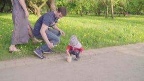 Le petit garçon avec des jeunes peint plus loin la craie sur l'asphalte Mouvement lent banque de vidéos