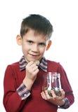 Le petit garçon avec la pièce de monnaie et le verre cognent la tirelire d'isolement Images libres de droits