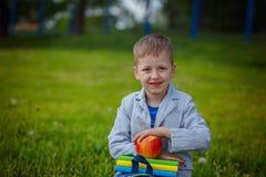 Le petit garçon avec la pile des livres et la nature rouge d'appleon verdissent le backg Image stock