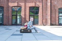Le petit garçon avec le jouet d'ours de nounours s'assied sur la valise Image stock