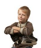 Le petit garçon avec les patins dans le chandail. Image libre de droits