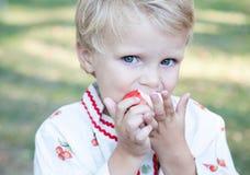 Le petit garçon avec mange la pomme Image libre de droits