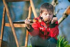 Le petit garçon avec plaisir mange les légumes grillés Photographie stock libre de droits