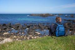 Le petit garçon avec le sac à dos bleu, s'assied sur la terre à la roche irlandaise de côte, à côté de la mer image libre de droits