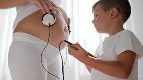 Le petit garçon avec le téléphone portable a à disposition mis des écouteurs sur le ventre de la femme enceinte banque de vidéos