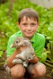 Le petit garçon avec un lapin dans les mains Photographie stock libre de droits