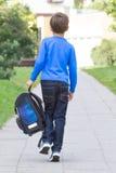 Le petit garçon avec un sac à dos vont à l'école Vue arrière photographie stock