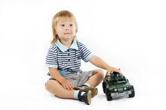 Le petit garçon avec un véhicule militaire de jouet Photo libre de droits