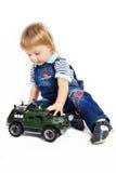 Le petit garçon avec un véhicule militaire de jouet Photographie stock libre de droits