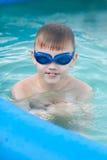 Le petit garçon ayant le bon temps dans la piscine Photo libre de droits