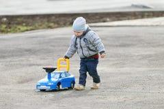 Le petit garçon beau dans le gris joue avec la voiture de jouet Photo stock