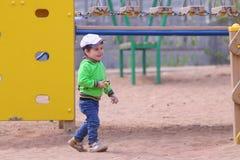 Le petit garçon beau joue avec la voiture de jouet sur le terrain de jeu d'enfants Image libre de droits