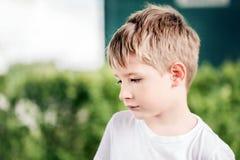 Le petit garçon blond caucasien mignon, un peu triste ou lancent, dans un jardin Photographie stock