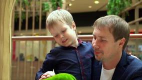 Le petit garçon blond joue avec un jouet mou au centre commercial Le père avec le fils considèrent un jouet dans le commerce banque de vidéos