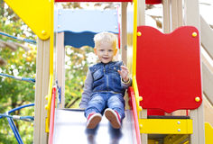 Le petit garçon blond s'assied sur une glissière d'enfants au terrain de jeu Photos libres de droits