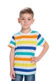 Le petit garçon blond se tient contre le blanc images stock