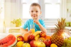 Le petit garçon boit du jus frais avec des fruits dans la cuisine Image stock