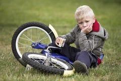 Le petit garçon bouleversé s'assied près à son vélo Photo libre de droits