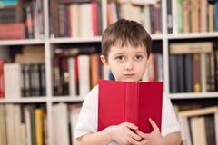 Le petit garçon cache le visage derrière le livre Photographie stock libre de droits