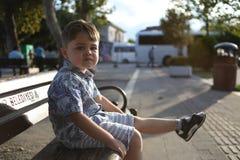 le petit garçon caucasien mignon s'assied sur un banc et fait des visages images stock