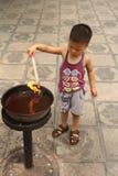 Le petit garçon chinois est encens brûlant dans le temple Photographie stock libre de droits