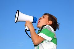 Le petit garçon, contre le ciel, crie dans le haut-parleur Image stock