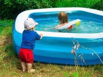 le petit garçon d'enfant en bas âge observe avec l'intérêt sur le côté de la piscine pour sa natation de soeur dans l'eau T images stock