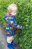 Le petit garçon d'enfant en bas âge sous la pluie vêtx, dehors Photographie stock libre de droits
