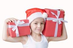 Le petit garçon dans le chapeau et le T-shirt du ` s de Santa tient deux boîtes de cadeaux o Photos libres de droits