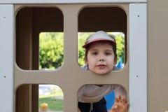 Le petit garçon dans le chapeau regarde dans la fenêtre dans la maison en bois Photographie stock