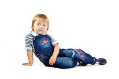 Le petit garçon dans des combinaisons bleu-foncé Photo libre de droits