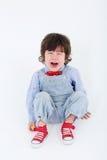 Le petit garçon dans la salopette bleue s'assied sur le plancher et pleure Images stock