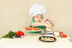 Le petit garçon dans le chapeau de chefs frotte sur le fromage de râpe pour la pizza Image stock
