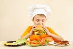 Le petit garçon dans le chapeau de chefs goûte l'hamburger cuit Photos stock