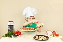 Le petit garçon dans le chapeau de chefs met un fromage râpé sur la croûte de pizza Photo libre de droits