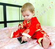 Le petit garçon dans le costume de vacances touche l'écran de téléphone Images libres de droits
