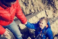 Le petit garçon de aide de main a aidé par le père en montagnes Photographie stock libre de droits