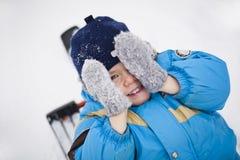 Le petit garçon de sourire cache son visage avec ses mains dans des mitaines Jour d'hiver Image stock
