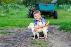 Le petit garçon de sourire embrasse affectueusement un chat rouge extérieur image libre de droits