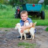 Le petit garçon de sourire embrasse affectueusement un chat rouge extérieur photos libres de droits