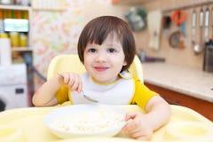 Le petit garçon de sourire mange le quark avec la crème sure Photographie stock