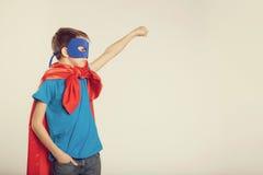 Le petit garçon de super héros dans le costume a soulevé sa main  Copyspace, modifié la tonalité Images libres de droits