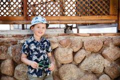 Le petit garçon de touristes est photographié avec un chat Photos libres de droits