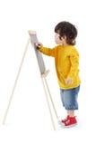 Le petit garçon dessine avec la craie sur le tableau d'isolement Photo stock