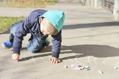 Le petit garçon dessine sur l'asphalte photo stock