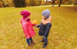Le petit garçon donnant l'érable d'automne laisse à la fille Image stock