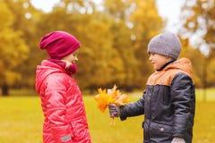 Le petit garçon donnant l'érable d'automne laisse à la fille Photos stock